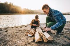 El papá enseña a su hijo a encender el fuego Imagen de archivo