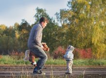 El papá enseña a su hijo a sentarse en la silla de montar Fotografía de archivo libre de regalías