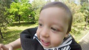 El papá es tiro su bebé del hijo en la calle entre los árboles almacen de metraje de vídeo