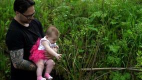El papá está deteniendo a una hija en sus brazos