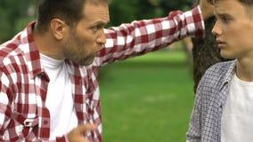 El papá estricto regaña al hijo debido al comportamiento perturbador, respecto del padre, disciplina almacen de video