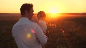 El papá feliz camina con su pequeña hija en campo Familia que descansa en parque en la puesta del sol El papá lleva adentro las m almacen de metraje de vídeo