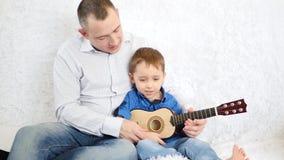 El papá feliz enseña al hijo a tocar la guitarra almacen de video