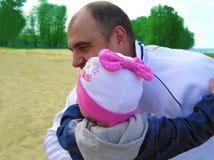 El papá feliz mantiene a la hija sus brazos Foto de archivo libre de regalías