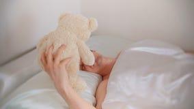 El papá joven del padre despierta y encuentra un oso del juguete en cama después de una noche dura con un niño almacen de video