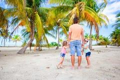 El papá joven y las pequeñas hijas en arboleda de la palma durante la playa vacation Fotografía de archivo libre de regalías