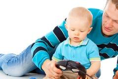 El papá juega con el bebé en la palanca de mando imagen de archivo