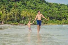 El papá juega con su hijo en el mar Fotografía de archivo libre de regalías