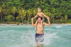 El papá juega con su hijo en el mar Fotografía de archivo