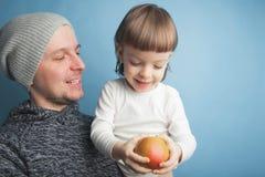 El papá juega con un pequeño hijo precioso, sentándose en sus brazos en un fondo azul en el estudio Lo divierte con Apple y ellos imagenes de archivo