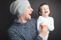 El papá juega con un pequeño hijo precioso, sentándose en sus manos en un fondo negro en el estudio Lo divierte con Apple y ellos fotografía de archivo