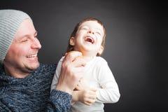 El papá juega con un pequeño hijo precioso, sentándose en sus manos en un fondo negro en el estudio Lo divierte con Apple y ellos imagen de archivo libre de regalías