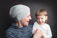 El papá juega con un pequeño hijo precioso, sentándose en sus manos en un fondo negro en el estudio Lo divierte con Apple y ellos foto de archivo libre de regalías