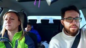 El papá, la mamá y el hijo de la familia comen en el bocadillo del coche y el café de la bebida metrajes