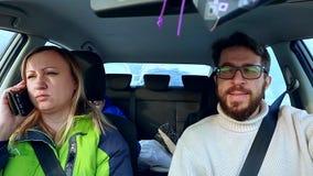 El papá, la mamá y el hijo de la familia entran en el coche en el camino del invierno almacen de video