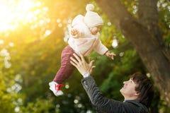 El papá lanza para arriba a la muchacha en parque del otoño Fotografía de archivo libre de regalías