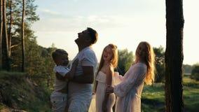 El papá lanza a su hijo en sus brazos Los padres y los niños en la ropa y el sombrero de paja blancos son felices metrajes