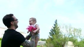 El papá lanza a una hija sonriente para arriba metrajes