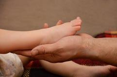 El pap? lleva a cabo el pie de un peque?o ni?o La mano masculina est? llevando a cabo una pierna del beb? Pie del beb? en la mano imagen de archivo