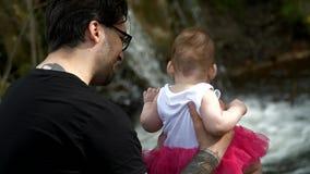 El papá muestra a su hija una cascada