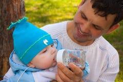 El papá permite beber de una botella al hijo Foto de archivo