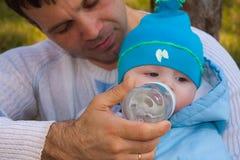 El papá permite beber el agua de una botella a t Fotos de archivo