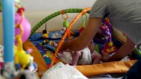 El papá pone a su pequeña hija en una manta con los juguetes metrajes