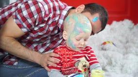 El papá ríe la mirada sobre sus cabezas cubiertas en hijo de la pintura almacen de metraje de vídeo