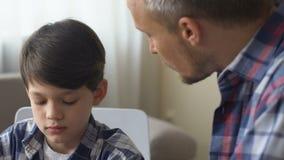 El papá regaña a su hijo para el mún comportamiento, discute disciplina de niño, sigue siendo tranquilo metrajes