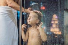 El papá se lava el pelo del ` s del hijo en la ducha por la tarde antes de ir a dormir en el fondo de una ventana con una visión  fotos de archivo