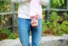 El papá sostiene el al aire libre al revés del bebé Imagen de archivo libre de regalías