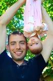 El papá sostiene el al aire libre al revés del bebé Foto de archivo libre de regalías