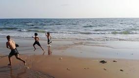 El papá toma en los niños de la cámara que funcionan con a niños en la playa metrajes