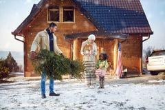 El papá trae el árbol de navidad para su pequeña hija imagenes de archivo