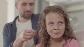 El papá trenza hija linda del pelo rizado a la pequeña Relaciones de familia almacen de video