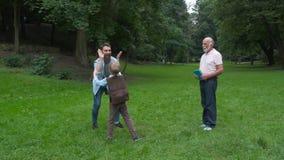 El papá y el abuelo encuentra a su hijo de la escuela primaria funcionamientos alegres del niño en los brazos de sus padres Opini almacen de metraje de vídeo