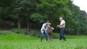 El papá y el abuelo encuentra a su hijo de la escuela primaria funcionamientos alegres del niño en los brazos de sus padres Opini metrajes