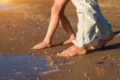 El papá y el hijo caminan en la playa descalzo imagenes de archivo