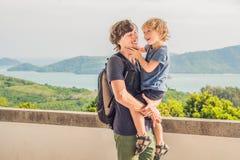 El papá y el hijo en el fondo de la playa tropical ajardinan panorama El océano hermoso de la turquesa renuncia con los barcos y fotografía de archivo libre de regalías