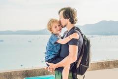 El papá y el hijo en el fondo de la playa tropical ajardinan panorama El océano hermoso de la turquesa renuncia con los barcos y fotografía de archivo