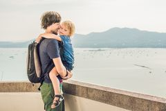 El papá y el hijo en el fondo de la playa tropical ajardinan panorama El océano hermoso de la turquesa renuncia con los barcos y imágenes de archivo libres de regalías