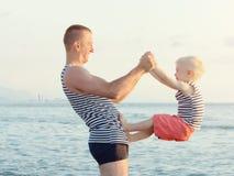 El papá y el hijo están jugando en la playa Pasatiempo de la diversión imagenes de archivo