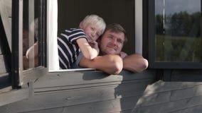 El papá y el hijo miran hacia fuera la ventana y agitan sus manos metrajes