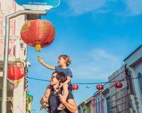 El papá y el hijo son turistas en la calle en el estilo portugués Romani en la ciudad de Phuket También llamó Chinatown o el viej fotografía de archivo