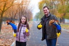 El papá y la hija con las escobas se colocan en el parque del otoño Imagen de archivo libre de regalías