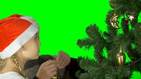 El papá y la hija en los casquillos Papá Noel del rojo adorna el árbol de navidad antes de la Navidad Preparación para la celebra metrajes