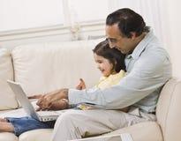 El papá y la hija miran la computadora portátil Fotografía de archivo