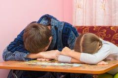 El papá y la hija se cayeron dormido en la tabla que recogían la imagen de rompecabezas Imagen de archivo libre de regalías
