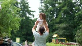 El papá y la hija se divierten en el parque El padre lanza a la muchacha para arriba Fin de semana de la familia Amor del ` s del almacen de metraje de vídeo