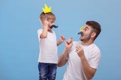 El papá y su hijo miran uno a sorprendieron en un fondo azul Foto de archivo libre de regalías